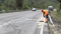 Un operari netejant la carretera en el punt de la C-14 on s'ha produït un accident entre tres turismes i un autobús