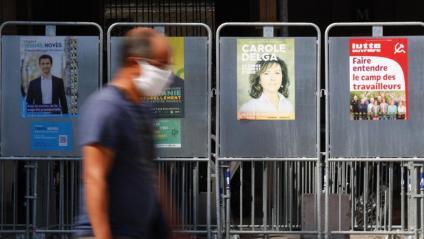 Un vianant passa per davant  d'una tanca amb cartells electorals  a Montpeller