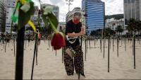 Una dona posa una rosa en un memorial pels morts pel virus a Rio de Janeiro