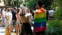 Un noi amb una bandera LGTBI durant un acte contra les agressions a aquest col·lectiu