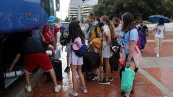 Un gup de nens i nenes carregant maletes i motxilles en un autocat