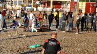 Un mosso observa gent a la platja de Barcelona durant el desallotjament a les 6h per donar pas als operaris de la neteja