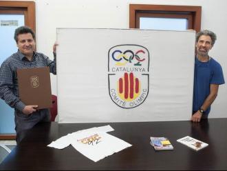 Xavier Vinyals i Francesc Serra Vinyals, amb una bandera del COC del 1992, la sol·licitud oficial d'ingrés al COI del 1991 i altres productes que van fer.