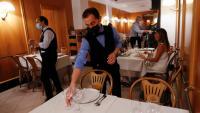 Un cambrer amb mascareta para la taula en un restaurant de Roma, a Itàlia