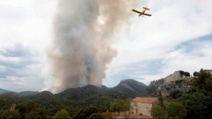 Un hidroavió passa sobre el castell de Santa Maria de Miralles. L'incendi de la Conca de Barberà i l'Anoia segueix actiu aquest diumenge