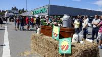 En un primer pla del taüt i garrafes de palla amb la mobilització dels pagesos de fons davant el Mercadona de Vic