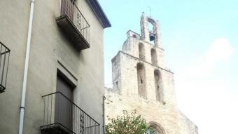 Mossèn Ramon Pijoan davant del temple de Santa Maria dels Turers, al centre de Banyoles, assenyalant el campanar amb les campanes que han generat la polèmica