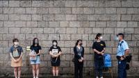 Un policia atura i identifica manifestants fora del tribunal que va condemnar Tong Ying-kit a nou anys de presó