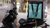 La motocicleta d'un repartidor amb la bossa de Deliveroo