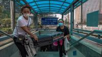 Dues dones amb mascareta protectora pugen les escales d'un passatge subterrani amb el seu equipatge a Pequín