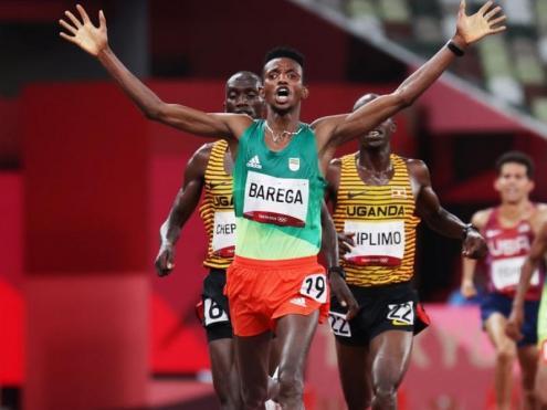 Barega alça els braços per davant dels ugandesos Cheptegei i Kiplimo