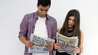 Dos joves llegeixen El Punt Avui i L'Esportiu