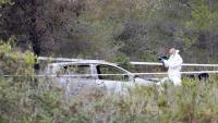 Un agents dels Mossos d'Esquadra fent fotos al cotxe on s'ha trobat una persona calcinada en una zona prop d'Albinyana