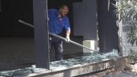 Operari traient els vidres trencats d'una de les façanes de la Fira de Barcelona
