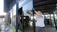 El propietari d'un dels locals afectats retira un vidre fet miques