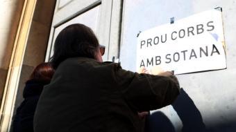 Dues persones enganxant cartells a les portes de l'arquebisbat de Tarragona al febrer de 2019