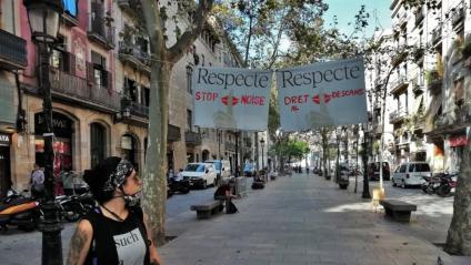 Una dona observa les pancartes que demanen respecte al passeig del Born, un dels punts de botellot a la ciutat de Barcelona