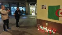Un individu observant el lloc on es va produir l'assassinat, el passat 8 d'octubre, amb una bandera d'Algèria i espelmes d'homenatge