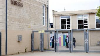 Pla general de l'exterior de l'institut de Vidres, amb agents dels Mossos d'Esquadra al darrere de la tanca.