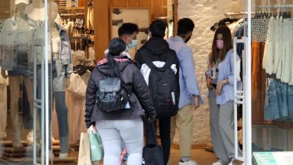 Compradors entrant en una botiga de roba al carrer Portal de l'Àngel de Barcelona.